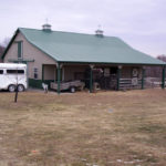 horse barn with green metal roof and cupolas