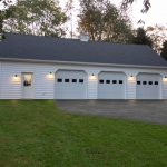 white pole barn garage with three doors and asphalt shingles